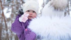 Op de achtergrond van het de winterbos, een portret van een klein éénjarig meisje in een grappige hoed met een bumbon Het meisje stock footage