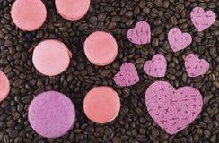 Op de achtergrond van koffiebonen, het gebakje van de chocolademacaroni met roze harten van liefde Stock Afbeelding