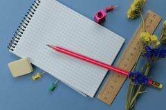 Op de blauwe oppervlakte van de lijst zijn kantoorbehoeften Het concept onderwijs stock afbeeldingen