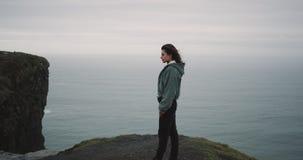 Op de bovenkant van Klippen bewondert een jonge vrouw het landschap, zij voelen zo geïmponeerd van het landschap dat zij rond hee stock video
