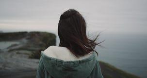 Op de bovenkant van Klippen een brunette een meditatie heeft, bewondert zij rond al landschap en is zeer geïmponeerd van mening stock footage