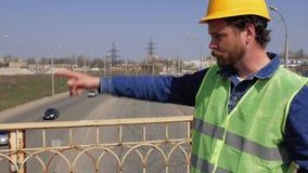 Op de brug is een voorman met een baard en snor in een gele helm en geeft instructies 4K video stock footage