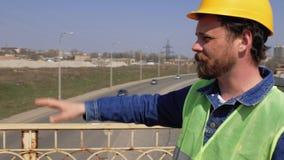 Op de brug is een voorman met een baard en snor in een gele helm en geeft instructies 4k-videoavoorman met een baard en stock videobeelden