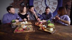 Op de houten lijst in het restaurant zijn er heel wat vegetarische snacks, op de achtergrond is een bedrijf van vrienden stock footage