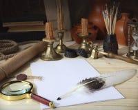 Op de houten lijst zijn: een rol met een verbinding, bladen van Witboek, een gansveer, een inktpot, leeswijzers, een vergrootglas Stock Afbeeldingen