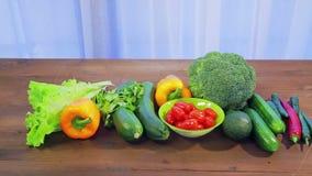 Op de houten lijst zijn verse groentencourgette, broccoli, sla, avocado, komkommers, peper en Spaanse peperpeper, kersentomaten stock video