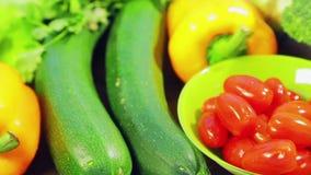 Op de houten lijst zijn verse groentencourgette, broccoli, sla, avocado, komkommers, peper en Spaanse peperpeper, kersentomaten stock videobeelden