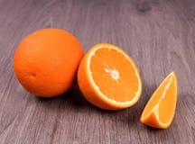 Op de houten oppervlakte zijn gehele oranje en verschillend gesneden sinaasappelen †‹â€ ‹ royalty-vrije stock afbeelding