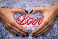 Op de liefde van de hoofdkusseninschrijving Vrouwelijke hand met zwarte manicure Stock Afbeelding