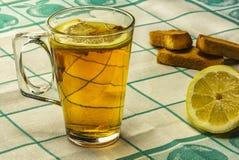 Op de lijst is een glas thee met citroen en liggen vanillebiscui Stock Foto
