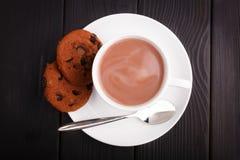 Op de lijst een kop van koffie met melk en een paar chocoladekoekjes Stock Afbeelding