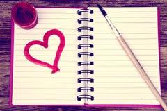 Op de lijst is een open roze notitieboekje; een notitieboekje waarop met een verfborstel en een roze hart geschilderd is royalty-vrije stock foto's