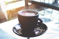 Op de lijst is er een zwarte koffiekop royalty-vrije stock afbeeldingen
