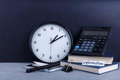 Op de lijst is inschrijvingsinformatie, naast een horloge, verscheidene boeken, een calculator, een blocnote en een klem royalty-vrije stock fotografie