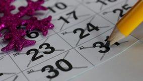 Op de lijst is de kalender van December van het Nieuwjaar Een hand streept de datum van 31 December in potlood door, close-up, stock footage