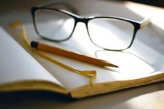 Op de lijst leg Blocnote, gele potlood en glazen royalty-vrije stock afbeeldingen