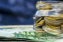Op de lijst, papiergeld en een glasbank met pence Stock Foto