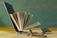 Op de lijst zijn boeken en open laptop royalty-vrije stock afbeeldingen