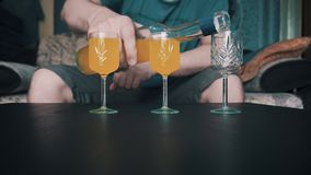 Op de lijst zijn drie stapels en een mens giet een gele cocktail in hen Sluit omhoog Heerlijke drank stock video