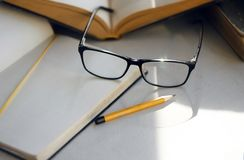 Op de lijst zijn er encyclopedieën, een notitieboekje, een potlood en elegante glazen royalty-vrije stock foto