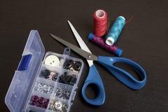 Op de oppervlakte van de lijst is een vakje met het naaien van toebehoren Naast een paar rollen van draad en schaar Stock Afbeeldingen