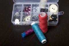 Op de oppervlakte van de lijst is een vakje met het naaien van toebehoren Verscheidene rollen van draad liggen naast elkaar Royalty-vrije Stock Afbeelding