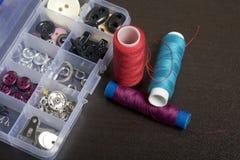 Op de oppervlakte van de lijst is een vakje met het naaien van toebehoren Verscheidene rollen van draad liggen naast elkaar Stock Foto
