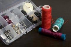 Op de oppervlakte van de lijst is een vakje met het naaien van toebehoren Verscheidene rollen van draad liggen naast elkaar Royalty-vrije Stock Foto's