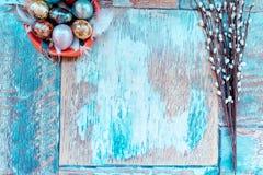 Op de oude houten lijst is een plaat van gekleurde paaseieren van kwartels en kip met gekleurd kant, en wilg Royalty-vrije Stock Foto's