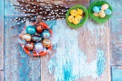 Op de oude houten lijst is een plaat van gekleurde paaseieren van kwartels en kip met gekleurd kant, en wilg Stock Afbeeldingen