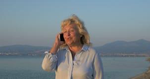 Op de overzeese kuststad van Perea, loopt Griekenland vrouw en spreekt op mobiele telefoon stock video
