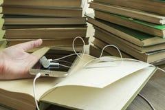 Op de pagina van het open boek is een smartphone en hoofdtelefoons royalty-vrije stock foto's