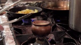 Op de pot van de fornuisklei met soep die koken, verwijdert de kok hete pan met tang stock video