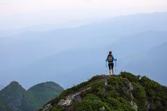 Op de rand van het kloof op het gazon onder de landschappen met hooggebergte en gebieden is er een toerist met een rugzak Stock Foto's