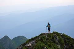 Op de rand van het kloof op het gazon onder de landschappen met hooggebergte en gebieden is er een toerist met een rugzak Stock Afbeelding