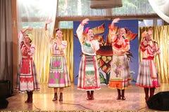 Op de stadium mooie meisjes in nationale Russische kostuums, toga's sundresses met trillend borduurwerk - volksmuziekgroep het Wi Stock Foto