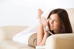 Op de telefoon: jonge vrouw die binnen zitkamer roept Stock Foto
