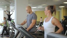 Op de tredmolenmens en een vrouwenbegin die op tredmolen in gymnastiek lopen stock video
