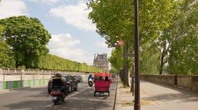 Op de Tuileries-dijk zijn er auto's, motorfietsen met pa's stock afbeelding