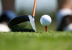 Op dicht beeld van een golfbal op T-stuk met club royalty-vrije stock fotografie