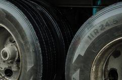 Op dicht bij de banden van een ladingsvrachtwagen, zwarte die banden met vuil door regen in een stad wordt veroorzaakt stock afbeelding