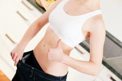 Op dieet zijnde vrouw met overmaatse broek stock foto
