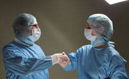 OP doctors shaking hands after successfull work. Two OP doctors shaking hands after successfull work royalty free stock photo