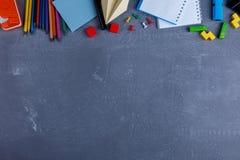 Op een achtergrond met een plaats voor inschrijving, de lay-out van notitieboekjes, kleurrijke potloden, kleine krijt en klemmen Stock Fotografie