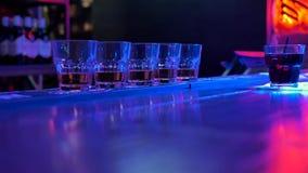 Op een barteller in een donkere ruimte zijn er vijf glazen met alcohol en drank stock videobeelden