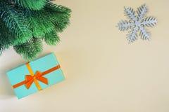 Op een beige achtergrond vertakken een gift zich in een turkooise doos met een oranje boog, een sneeuwvlok en een spar een plaats stock foto's
