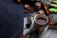 Op een donkere oppervlakte een kop thee, een raad met zoete peperkoeken, takjes van een boom en verscheidene brandende kaarsen Royalty-vrije Stock Foto's