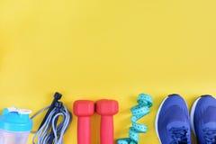 Op een gele achtergrond gefotografeerde tennisschoenen, touwtjespringen, domoren en een fles De ruimte van het exemplaar Geschikt Stock Fotografie