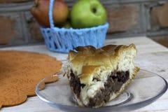 Op een glasplaat ligt een stuk van cake met appeljam wordt gevuld met kersen, okkernoten en appelen in een mand die stock fotografie
