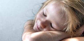 Op een grijze achtergrond ligt een slaap glimlachend meisje in de stralen van de zonochtend royalty-vrije stock foto